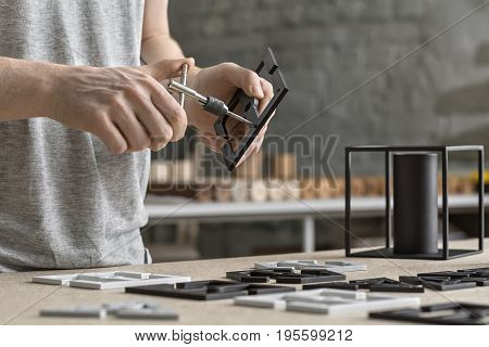 Worker is using a t-wrench on the metal black billet in the workshop. On the table under his hands there are other white and black billets and a dark cylindrical construction. Closeup. Horizontal.