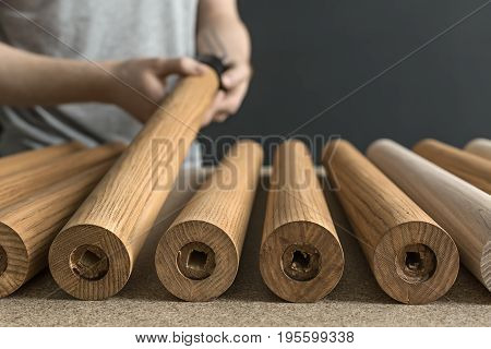 Wooden billets on the light tabletop in the workshop. Man with a tattoo is taking one of them. Closeup low aperture photo. Horizontal.