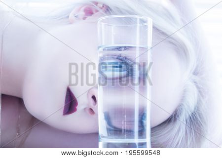 girl looks at camera through glass with water toned image