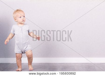 Cute blonde one year kid toddles against the grey background. Copy space.