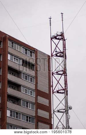 A big broadcasting radio tower inside a russian city near a building