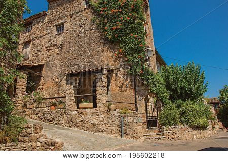 Les Arcs-sur-Argens, France. Old stone houses in alley under blue sky, at the gorgeous medieval hamlet of Les Arcs-sur-Argens. Provence region, Var department, southeastern France