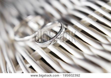 Pair of golden wedding rings on white rattan surface. Wedding details symbol of love and marriage.