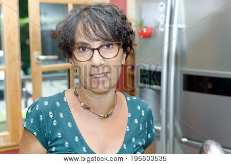 a portrait of a mature woman in the kitchen