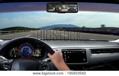 Hand on steering wheel driving on open road