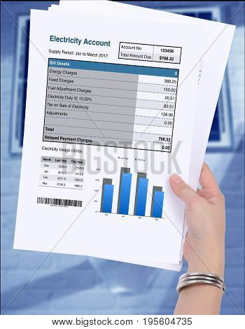 Electricity account bill in someone hand on blue background.
