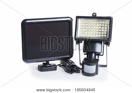 Small solar cell panel and LED light with movement sensor on white background.