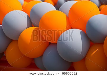 Orange and gray inflatable balls at a celebration activity