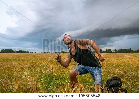 Young man with beard vaping an electronic cigarette. Vaper hipster smoke vaporizer in the yellow field. Man with tattoo and dredlocks. Funny shot.