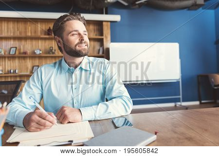 Portrait of jolly young man with beard sitting at table and holding pen in hands. He is leaning arms on paper sheets and looking up to distance with delight. Copy space in right side