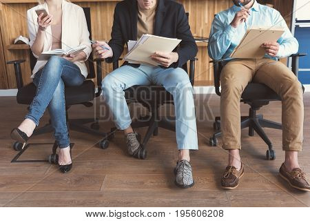 Close up of legs and bodies of two men with pens, clip board and papers in hands. Woman with open notebook on laps and mobile phone in hand sitting at office chair cross-legged next to males