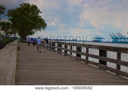 people walking on the boardwalk in the park