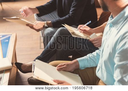 Close up of hands and legs of men and cross-legged woman sitting on chairs in office with pens and pieces of paper. She filling in some data