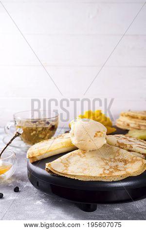 Dessert - Pancakes with mango Ice Cream and honey on stone background, copy space