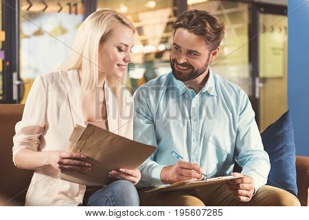 Waist up portrait of happy young bearded man and woman sitting on sofa in office hall keeping papers in hands. Guy is using clipboard and holding pen. Girl is looking at his writing