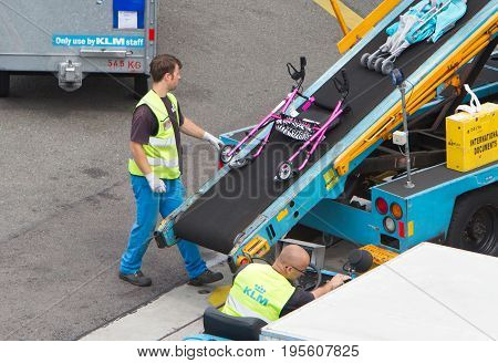 AMSTERDAM NETHERLANDS - JUNE 29 2017: Loading luggage in airplane at Amsterdam Schiphol airport Netherlands on June 29 2017. Schiphol is the fourth biggest airport in Europe.