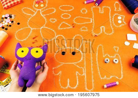 Workplace of a tailor: fabric spools measuring tape buttons needles bows toys and drawings. Girl holding purple cat