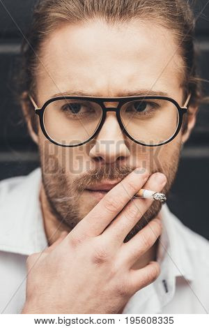 Close-up Portrait Of Handsome Stylish Young Man In Eyeglasses Smoking Cigarette