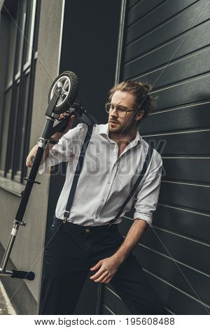 Stylish Young Man In Spectacles And Suspenders Holding Scooter While Standing Outside Modern Buildin