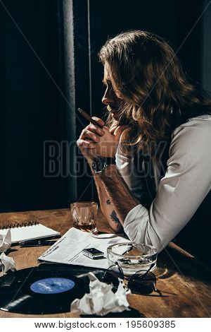 Handsome Young Bearded Man Smoking Cigar While Sitting At Table With Newspaper, Ashtray, Vinyl Recor