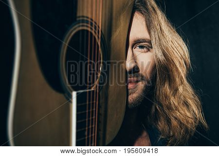 Close-up Portrait Of Handsome Bearded Long Haired Man Holding Guitar And Smiling At Camera