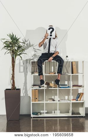 Stylish Young Businessman Holding Card With Question Mark While Sitting On Bookshelf In Office