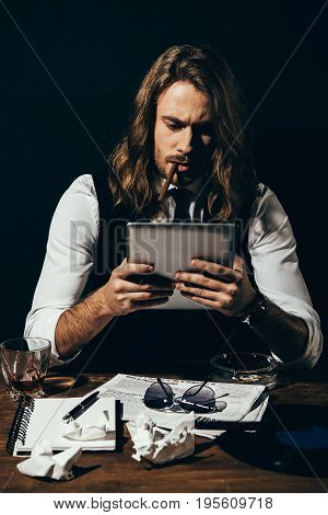 Handsome Young Stylish Man Using Digital Tablet While Smoking Cigar On Black