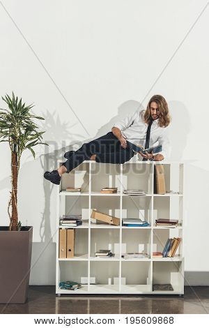 Stylish Young Businessman Lying On Bookshelf And Reading Book In Office