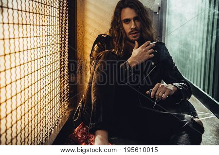 Stylish Bearded Long Haired Man In Leather Jacket Smoking Cigarette And Looking At Camera