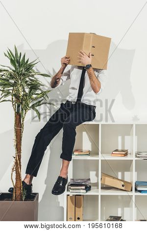 Stylish Young Businessman Hiding Face With Folder While Sitting On Bookshelf