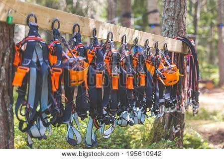 Climbing equipment in summer adventure park camp. Helmets and harnesses hanging on a board ready for extreme three forest exploration. Concept for summer adventures family time team building vacation.