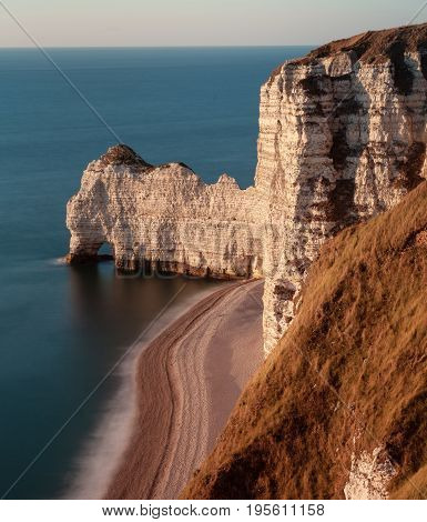 The pebbled beach, natural arch Porte d'Amont and coastline of Etretat, a commune in the Seine-Maritime department in the Normandy region of north western France