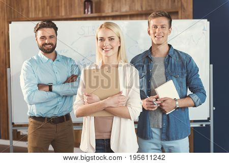 Portrait of happy young lady and two guys standing with their back to big flipchart and smiling. Girl is cuddling clipboard by hands. One man is holding notebook with pen and other one is folding arms