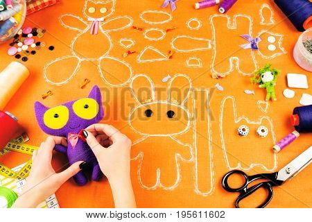 Workplace of a tailor: fabric spools measuring tape buttons needles bows toys and drawings. Girl nailing red bow to the purple cat