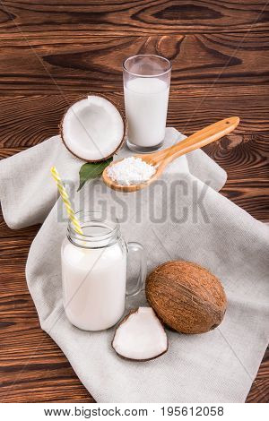 Mason jar and a glass full of fresh coconut milk with green leaves and wooden spoon with coconut chips on a light fabric and on a dark wooden background. A coco, coconut milk and nut chips.