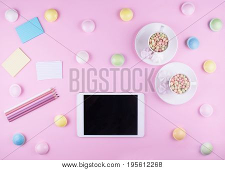 Workspace. Pink pastel flat lay with tablet, two cups, pencils and sweeties.
