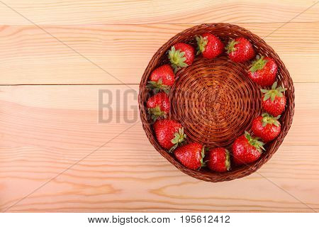 Nutritious red strawberries in a wooden basket on a light brown table. Bright red strawberries with green leaves forming a circle in the crate. Fresh tasteful berries in a brown box. Summer fruits.