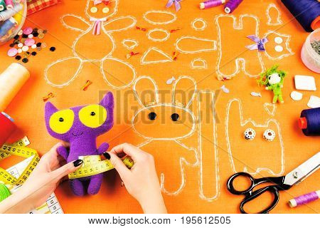 Workplace of a tailor: fabric spools measuring tape buttons needles bows toys and drawings. Girl measuring purple toy with the measuring tape