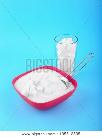 A pink box with crumbly sugar, and a glass with sugar crystals on a blue background. A small sieve in a box with sugar. The transparent glass full of sugar cubes.