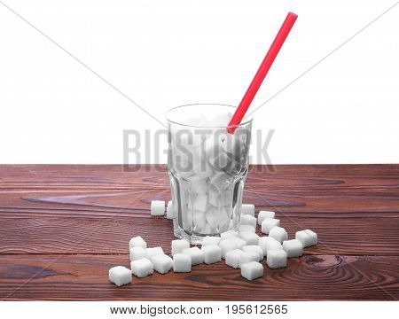 A complete glass of sugar cubes with long straw on a wooden table, isolated on a white background. Unhealthy sugar pieces on a brown table. The health risks related to diabetes and calorie intake.