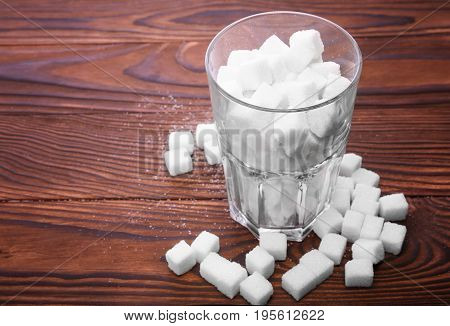 A glass of sugar crystals or cubes on a dark brown wooden table. A few sugar cubes are near the full glass with white sugar. Intake of bad calories.