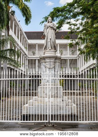 Port Louis Mauritius - December 25 2015: Statue of Queen Victoria Government House French Colonial building still used by the current government Port Louis Mauritius.
