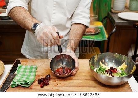 Chef is cooking salad dressing of red berries, oil and vinegar with whisker