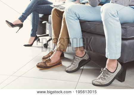 Close up of legs of young men sitting on office sofa and woman sitting cross-legged on chair on wheels in first in first out queue. One guy is having clipboard on his laps
