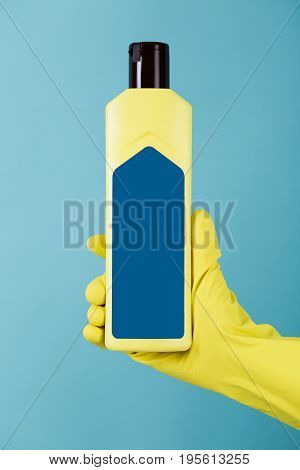Hand in a rubber yellow glove holds a bottle of liquid detergent on a blue background. cleaning