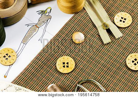 Workplace of a dressmaker: buttons spools measuring tape sketch fabric buckle and zipper