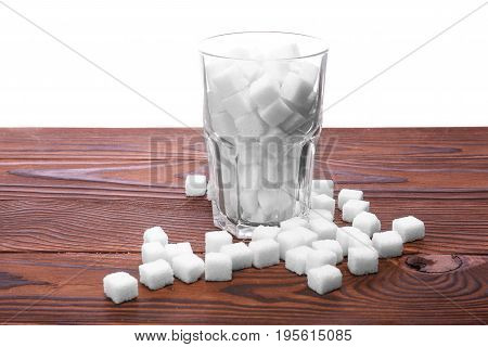 An entire glass of sweet sugar cubes on a table, isolated on a white background. White organic sugar on the dark brown wooden table. Consumption of bad calories.
