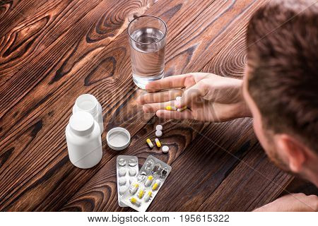A man is holding several tablets in hand on a dark brown wooden background. Two white medicine bottles, different antibiotics and a glass of water on the wooden table. The boy drinks pills.