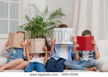 obscured view of children covering faces with books while reading at home