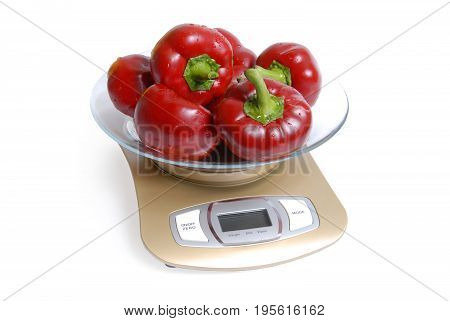 Red sweet peppers on scales on a white background